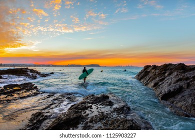 Surfer standing on the end of a rock with incoming ocean surf, and a colourful sunset at Currumbin Rock