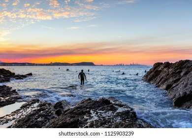 Surfer standing on the end of a rock with incoming ocean surf, and a colourful sunset at Currumbin Rock Gold Coast.