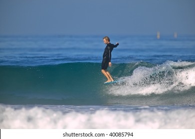 Surfer standing on the nose of his longboard on a clean wave