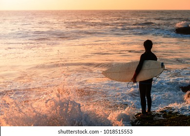 The surfer stands on the rocky ocean coast in anticipation of his waves