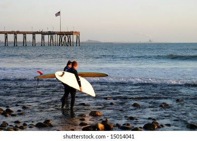 Surfer at sunset at the beach near the pier in Ventura California.