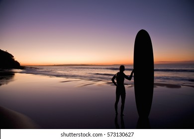 Surfer at sunset on the Sunshine Coast Queensland Australia.
