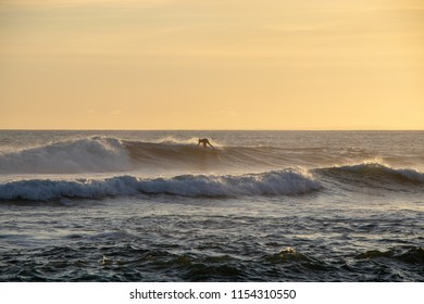 Surfer in sunset session riding a wave at Echo Beach Canggu Bali Indonesia