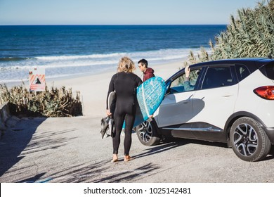 A surfer with a surfboard communicates with friends by surfers.