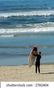 Surfer With Surfboard on California Beach