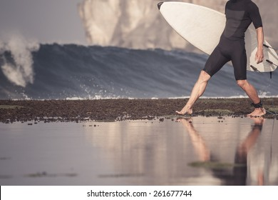 Surfer with surfboard on a coastline of Sumbawa, Indonesia