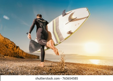Surfer with a surfboard running on the beach at sunset. Man runs with a SUP board. Male surfer lifestyle. Stand up paddleboard.