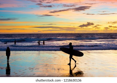 Surfer with surfboard walk on the beach at sunset. Bali island, Indonesia