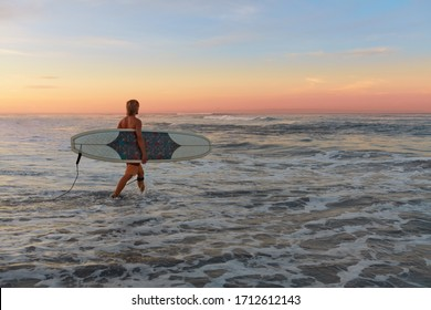 Surfer. Surfing Man With White Surfboard Walking In Ocean. Healthy Lifestyle, Water Sport. Beautiful Seascape, Attractive Tropical Sunset.
