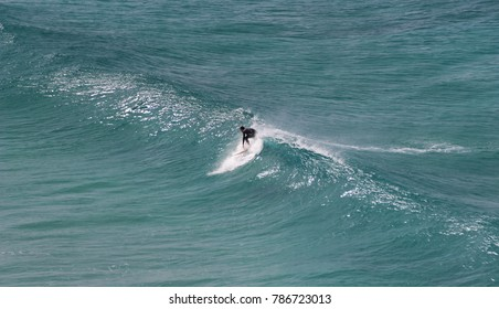 Surfer takes off on a wave