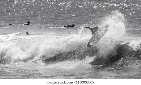 A surfer taking to the air and getting ready to land an air-reverse in black and white.
