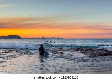 Surfer wading into the ocean at Currumbin Rock, with a colourful sunrise over Surfers Paradise