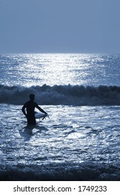 A surfer wading into the ocean waves under the moonlight.  Shot on location at Ocean City, MD, USA.