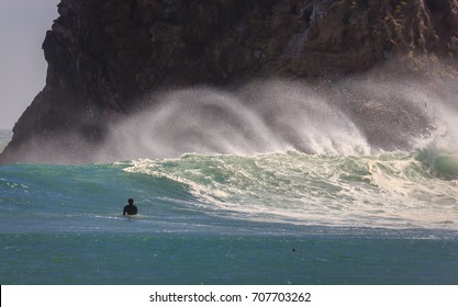 Surfer waits for wave with strong offshore breeze raising a tall spray