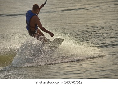 Surfer wakeboarding an jumping ollie at golden sunset. Skilled wakeboarder doing ollie jump, splashing water drops into the camera. Young man riding cable wake park on vacation