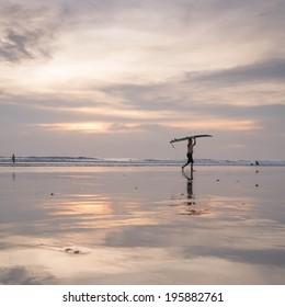 Surfer walk on Kuta beach during sunset hours - Shutterstock ID 195882761