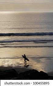 Surfer walking accross the beach at sunset. Trebarwith Strand, Cornwall, UK.