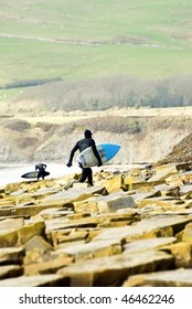 A surfer walking across a rocky coastline with beautiful green hills in the backround