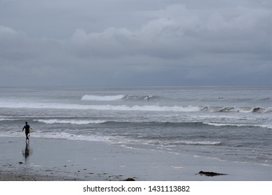 Surfer walking along an overcast beach in Carlsbad California 6/21/19