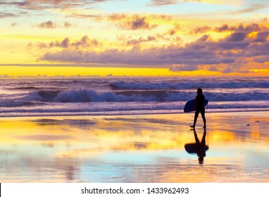 Surfer walking by the beach with surfboard at sunset. Bali, Indonesia