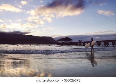 Surfer walking into the water in Hana lei Bay, Kauai HI.