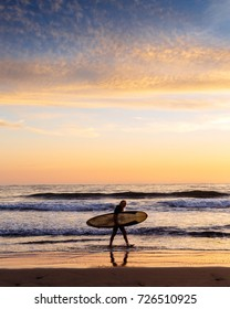 Surfer walking on the beach at sunset in San Diego CA