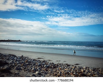 Surfer walking on beach with surf board. California, USA, pacific ocean coast. Blue cloudy sly in background.