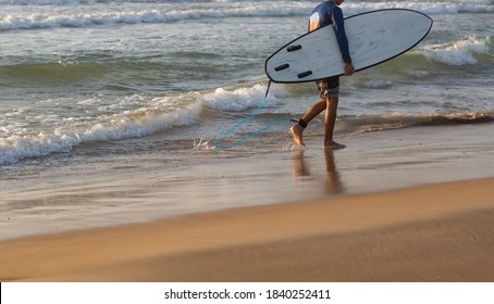 Surfer walking with surfboard on the beach. Summer time and active rest concept.