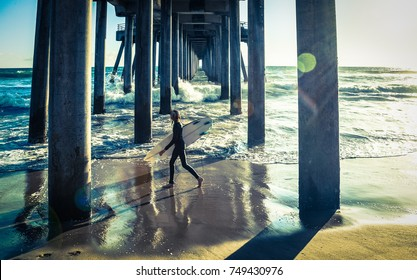Surfer walking under Huntington beach pier in southern California, vintage effect sunlight flare