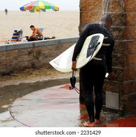 Surfer washes away sand under shower next to beach.