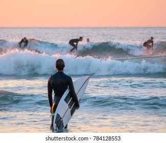 Surfer watching his friends surfing from the shore
