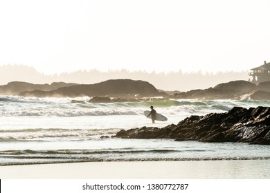A surfer wearing a wetsuit entering the ocean carrying a surfboard, with rock outcroppings, islands, and a beach house in the misty background, Tofino, British Columbia, Canada.