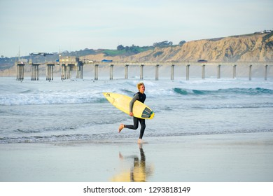 Surfer in wet suit holding a yellow surfboard on the beach. Surfer going out of the water and walking before sunset time, La Jolla Beach, San Diego, California, USA. 01/04/2019