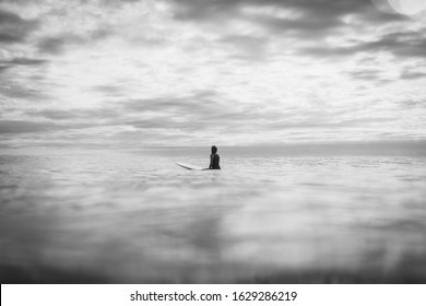 A surfer woman sitting on surfboard longboard - and waiting for the wave, New Zealand