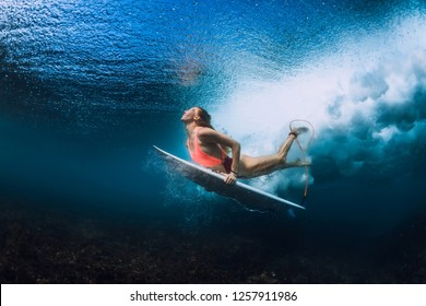 Surfer woman with surfboard dive underwater
