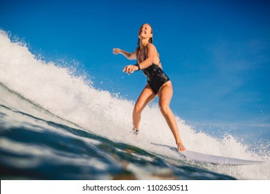 Surfer woman at surfboard ride on ocean wave. Woman in ocean during surfing.