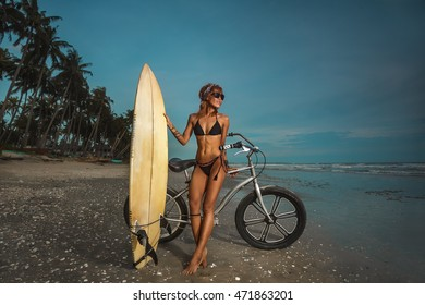 Surfer young woman on her bicycle on the beach