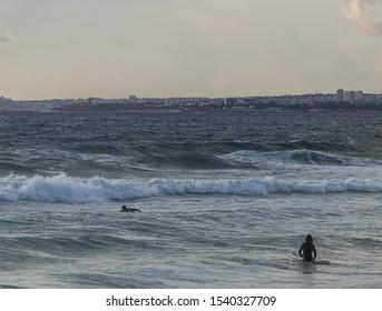 Surfers in autumn on the coast near Lisbon