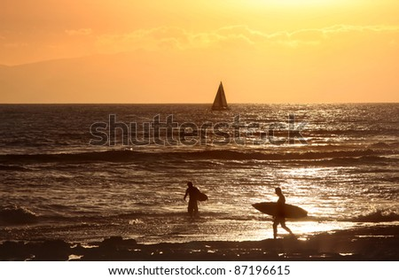 Surfers and boat in Sunset, Santa Cruz de Tenerife,   Spain,  Atlantic Ocean