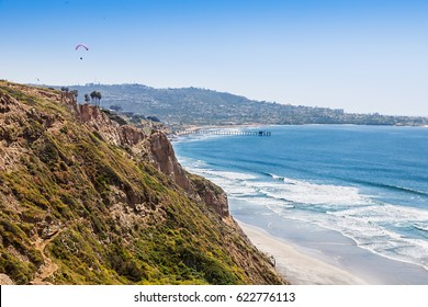 Surfers climb the steep path from the beach up the cliffs at Torrey Pines. Scripps Pier, La Jolla Shores and La Jolla Cove in the distance