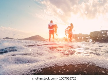 Surfers couple running with surf boards on the beach - Sporty people having fun in sunny day - Extreme sport, travel and vacation concept - Focus on bodies silhouettes - Water on camera lens