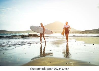 Surfers couple running together with surfboards on the beach at sunset - Sports friends having fun surfing - Travel, holidays, sport lifestyle concept