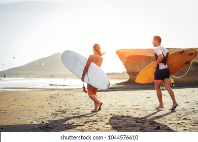 Surfers couple running together with surfboards on the beach at sunset - Sporty friends having fun going to surf - Travel, vacation, sport lifestyle concept