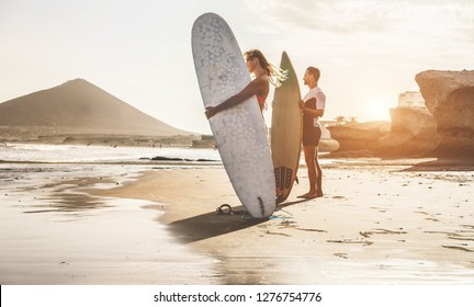Surfers couple waiting for the high waves on beach - Sporty people with surf boards at sunset - Extreme sport and vacation concept - Focus on female body