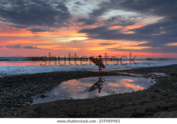 A surfer's destination, Playa Dominical in Costa Rica is a rocky beach settled mostly by foreign surfers. Sunset scene with surfers, waves and the setting sun reflecting in a tide pool.