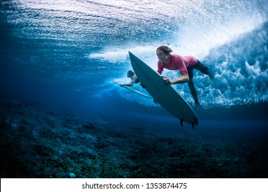 Surfers dive under the breaking wave