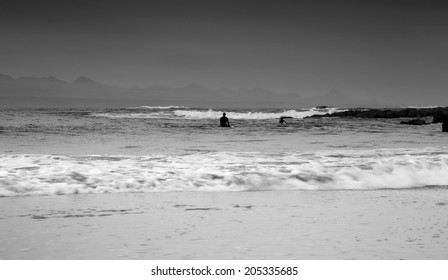 Surfers enjoying the waves on an overcast and rainy day