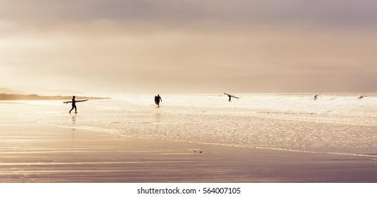 Surfers enjoying the waves on a winters day at Rest Bay in Wales, United Kingdom.