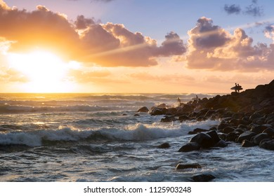 Surfers jumping into the ocean from the rocks at Bureigh Heads Gold Coast, with sunrise in the horizon