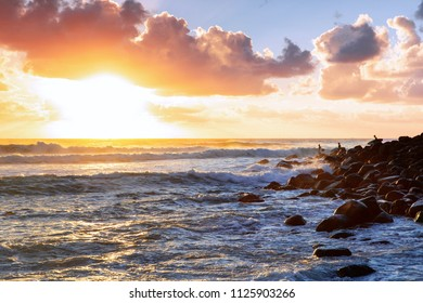 Surfers lining up on the ocean rocks at Burleigh Heads Gold Coast as the sun breaks over the ocean.